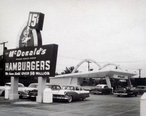 1955, Le premier restaurant ouvert par Ray Kroc. La mention « speedee service system » et les deux arches symbolique de McDonald's sont présentes. Le créateur de la marque aux hamburgers continue aujourd'hui à susciter l'admiration et est actuellement l'objet du film biographique « The Founder » qui sortira début 2017.