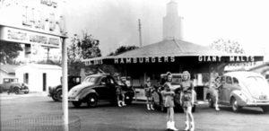 1940, le MacDonald's Bar-B-Q de San-Bernadino. Comme le veut le système drive-in, populaire à l'époque, les clients s'installent sur le parking en voiture et les serveuses apportent les repas directement à la voiture.
