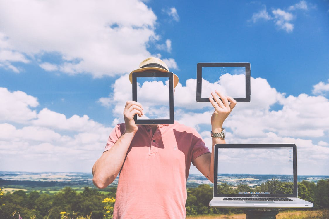 Standing Man Holding Ipads Near Macbook Pro