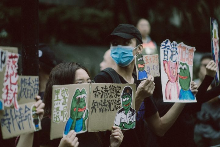 A group of people holding signs Description automatically generated